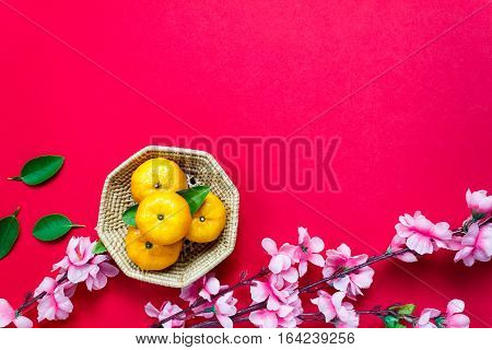 Top view orange leaf wood basket plum blossom on red background with copy space.
