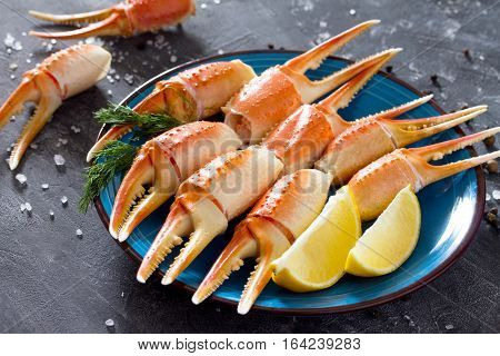 Cooked Crab Claws With Lemon, Sea Salt And Pepper On A Concrete Background.