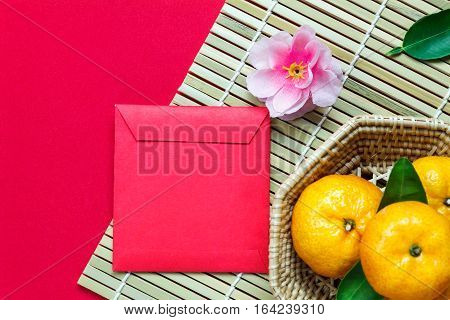 Top view accessories Chinese new year festival decorations.orange leaf wood basket red packet plum blossom on red background.