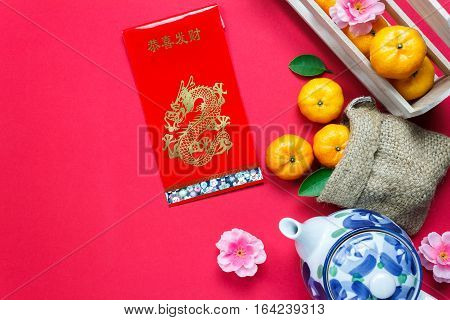 Top view accessories Chinese new year festival decorations.orange leaf wood basket red packet plum blossom teapot on red background.Foreign language means be rich and Happy.