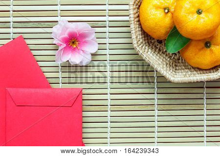 Top view accessories Chinese new year festival decorations.orange leaf wood basket red packet plum blossom on bamboo background with copy space.