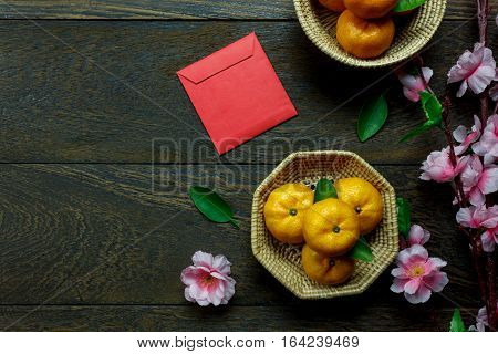 Top view accessories Chinese new year festival decorations.orange leaf wood basket red packet plum blossom on table wooden background with copy space.