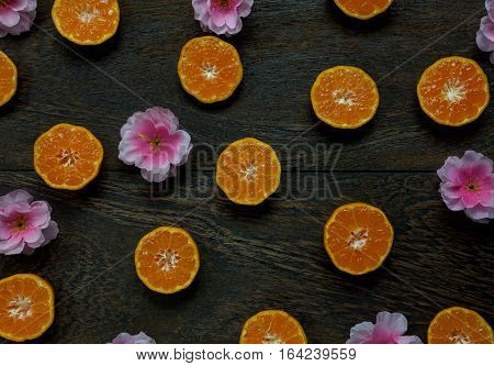 Top view accessories Chinese new year festival.orange sliced and beautiful pink plum blossom on wooden table background.