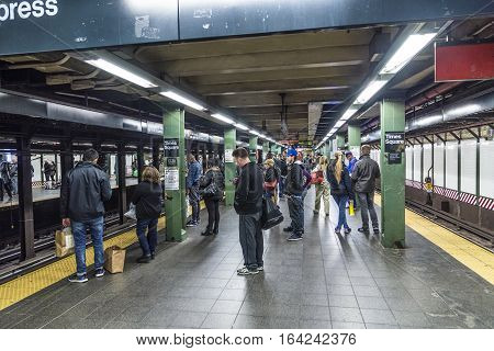 People Wait At A Subway Station In New York