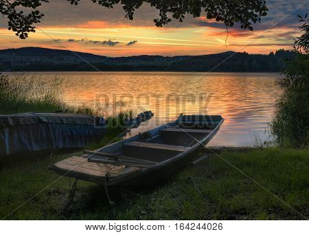 Rowboat on beautiful lake with dramatic sunset.The morning of the loch.Landscape with boat.A fishing boat tied at the shore of a Lipno lake Czech Republic.Nature landscape.