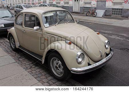 COPENHAGEN - MAY 16 2012: Vintage Volkswagen Beetle retro car parked at the famous Vesterbro District on Sankt Jorgens street in Copenhagen Denmark just after a rain shower May 16 2012