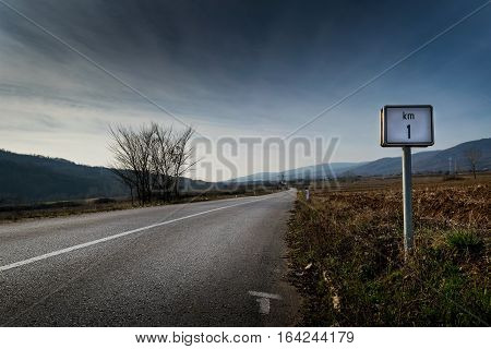 One kilometer sign on a country deserted road