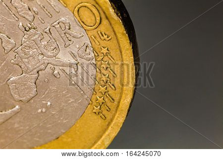 Euro coin macro, one euro. Close-up photography and details of one euro coin. Image taken with a macro professional lens. Gray background.