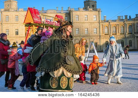 Gatchina, Russia - January 6, 2017: Christmas show for children on the parade ground in front of the Gatchina Palace. Maiden and Godmother dance in a circle with the children.