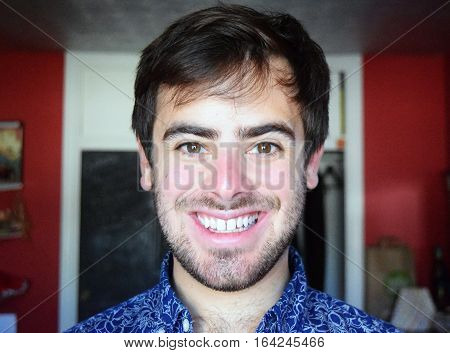 Portrait headshot of a handsome man smiling indoors