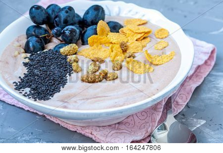 Chocolate smoothie bowl of cereal grapes and mulberries. Love for a healthy raw food concept.