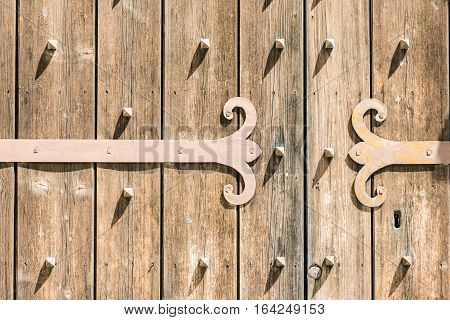 Detail of an old wooden door with metal hinge