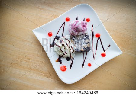 Blueberry ice cream with Chocolate brownie. Homemade brownies with vanilla ice cream and whipped cream.(selective focus)