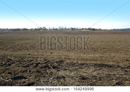 Country landscape with plowed field and a village far away on spring day