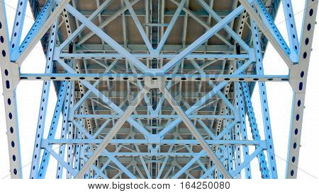 A close view of the intricate steel supports beneath a large bridge.