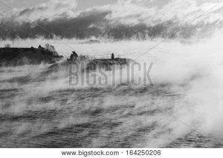 Small island with a lighthouse in misty steamy ocean at winter