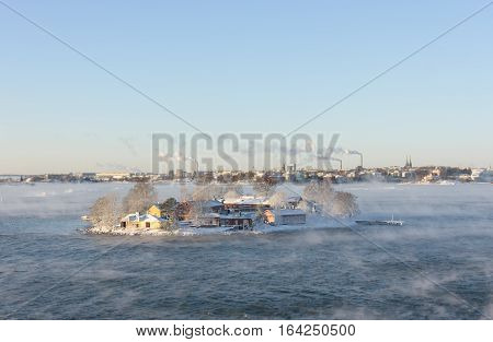 Small island in a steaming sea in Helsinki Finland at winter