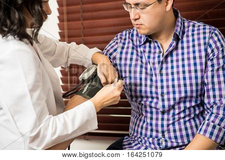 Checking Blood Pressure Of Patient
