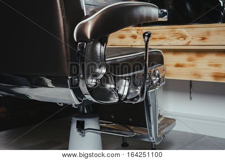 Close-up Stylish Vintage Barber Chair In Wooden Interior. Barbershop Theme