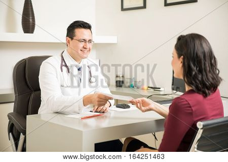 Doctor Handing Medical Prescription To Patient