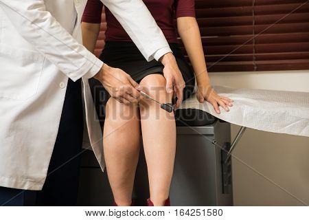 Doctor Checking A Woman's Reflexes