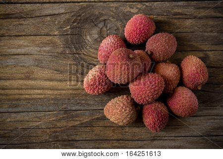 fresh red litchis on old wooden table