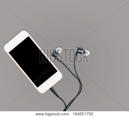 MP3 digital music player built into smartphone or mobile phone with earbuds against a grey background