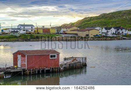 Little red shack on a dock in the small village and community of Twillingate, Newfoundland.  Sun sets brightly behind a hill in this coastal small Newfoundland community.