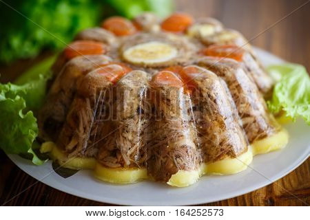 jellied meat with vegetables on a wooden table