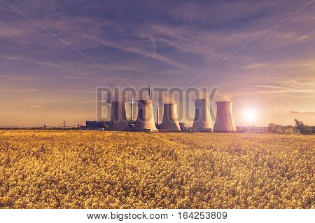 Thermal power plant at sunset sky, rape field