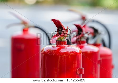 Red tank of fire extinguisher on the ground