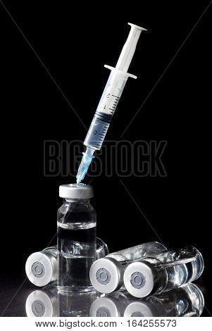 Glass Medicine Vials and Syringe on black background