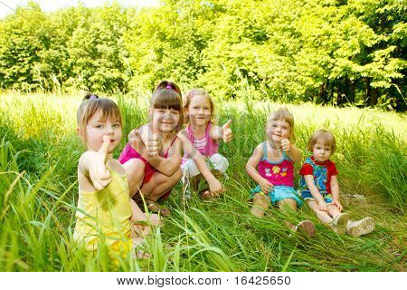Group of five happy kids sitting in the grass