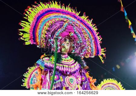 BAMNIA PURULIA WEST BENGAL INDIA - DECEMBER 23RD 2015 : Dancer performing at Chhau Dance festival. It is a Indian tribal martial dance at night based on Hindu myth. Shot under colored light.
