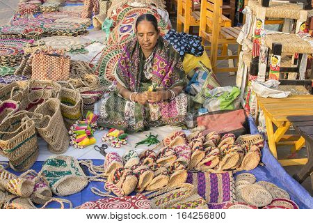 KOLKATA WEST BENGAL INDIA - DECEMBER 3RD 2016 : Unidentified woman preparing jute bags artworks of handicraft Handicraft Fair in Kolkata - the biggest handicrafts fair in Asia.