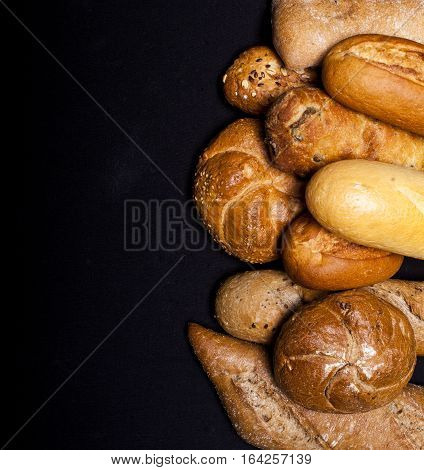 Assortment of baked goods on black table with free copy space for text. Top view.