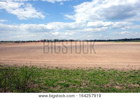 Country landscape with plowed field and a village far away on spring day. Horizontal view