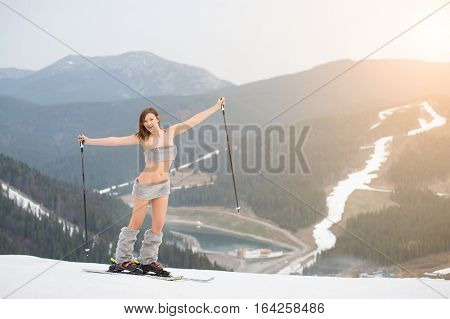 Happy Naked Female Skier Standing On The Snowy Slope Of The Mountain, Rising Hands Up, Wearing Ski E