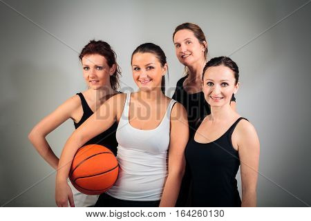 4 women aged between approx. 20 and approx. 40 playing basketball
