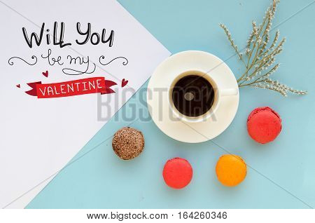 St Valentine's Day vintage overhead composition of note with love confession, macarons and coffee mug on tender blue background