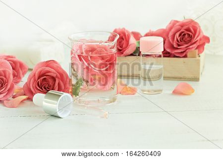Homemade rose facial tonic. Glass jar of flower attar, bottle, pippette. Aromatic and chemical-free morning cleansing freshness. Soft focus and light.
