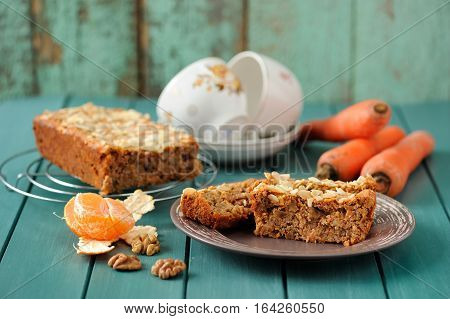 Homemade carrot cake with fresh carrots and clementines on turquoise background horizontal