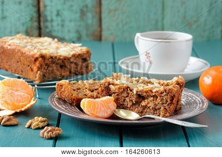 Homemade carrot cake with fresh clementines on turquoise background closeup