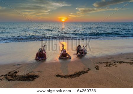 Three girls on the beach at sunset
