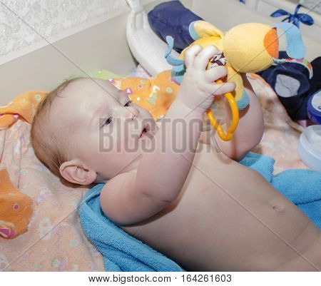 The boy at the age of 6 months lying down holding a toy