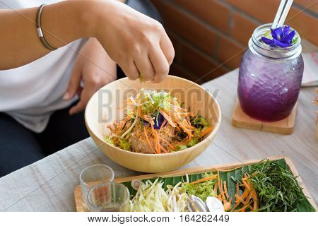 Woman mixing ingredients of Rice salad set on wood plate Khao yam Thai cuisine