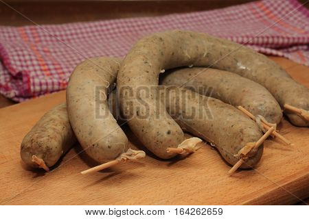 Three delicious sausage on a wooden cutting board