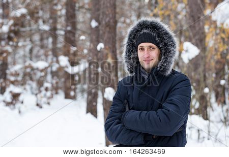 Young man stands in the winter forest. Man looks into the camera and smiles heartily.
