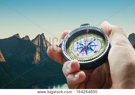 a compass and hand in a mountains