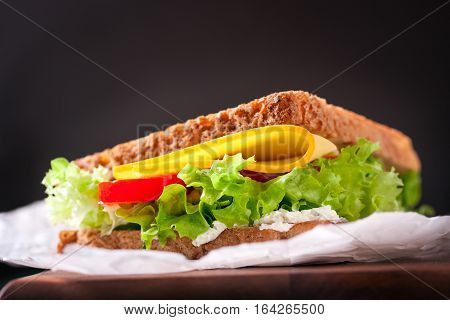 Toasted sandwich with salad leaves tomatoes and cheese with fork on a cutting board